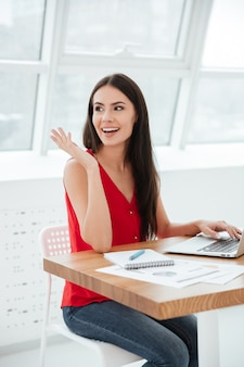 Imagem vertical de mulher de negócios de camisa vermelha e calça jeans, sentada à mesa com o laptop no escritório perto da janela e olhando para longe