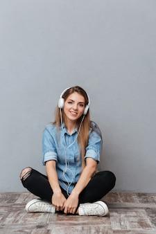 Imagem vertical de mulher ouvindo música no chão