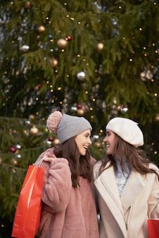 Imagem vertical de mulheres e uma grande árvore de natal