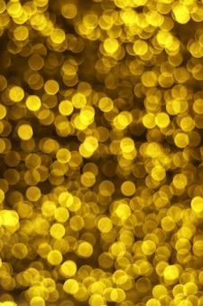 Imagem vertical de ouro desfocado luzes bokeh em fundo escuro