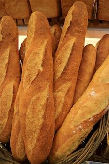 Imagem vertical de pães de baguete francês fresco feito em uma cesta
