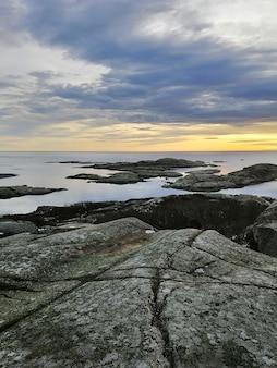 Imagem vertical de rochas cercadas pelo mar durante o pôr do sol em rakke, na noruega