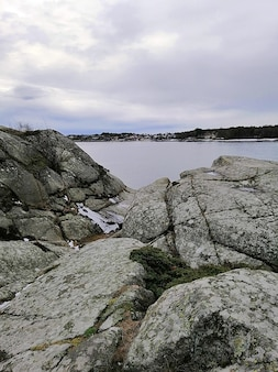 Imagem vertical de rochas cercadas pelo rio sob um céu nublado na noruega