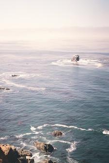 Imagem vertical de rochas no oceano perto da costa de um penhasco