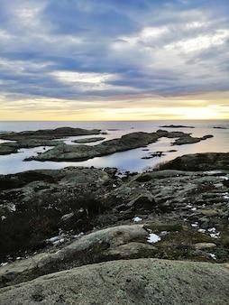 Imagem vertical de rochas rodeadas pelo mar durante o pôr do sol em rakke, na noruega
