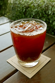 Imagem vertical de um copo de café gelado na mesa de madeira