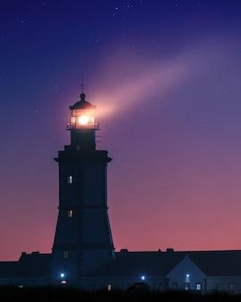 Imagem vertical de um farol sob um céu estrelado à noite