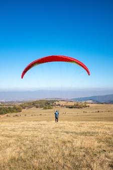 Imagem vertical de um homem voando com um pára-quedas vermelho cercado por vegetação sob um céu azul