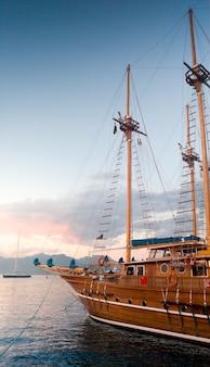 Imagem vertical de um lindo navio histórico de madeira no porto, aos raios de luz do pôr do sol