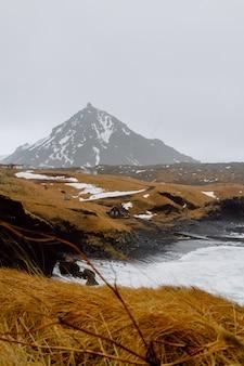Imagem vertical de um rio rodeado por colinas cobertas de neve e vegetação na islândia