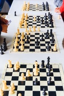 Imagem vertical de um torneio de xadrez com vários tabuleiros de jogo.