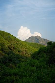 Imagem vertical de uma bela paisagem montanhosa contra nuvens e céu azul