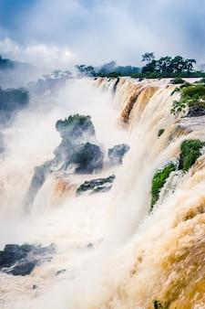 Imagem vertical de uma cachoeira cercada por vegetação coberta pela névoa sob um céu nublado