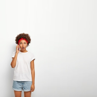 Imagem vertical de uma jovem estupefata conversa ao telefone com a irmã e descobre notícias chocantes