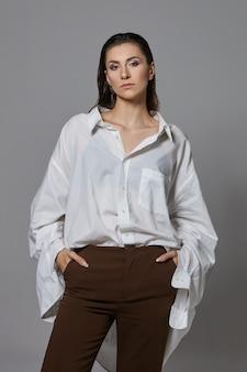 Imagem vertical de uma jovem europeia elegante e confiante com cabelo escuro penteado para trás, posando, vestindo uma calça marrom elegante e uma camisa branca grande demais, mantendo as mãos nos bolsos