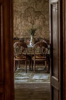 Imagem vertical de uma luxuosa sala de jantar com cadeiras ornamentadas, vista através de uma porta aberta