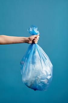 Imagem vertical de uma mão feminina segurando um saco de lixo com plástico, triagem de lixo e conceito de reciclagem