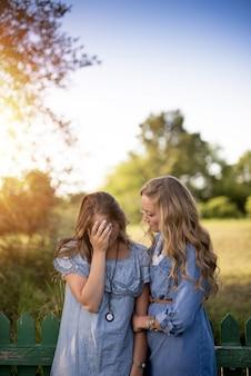 Imagem vertical de uma mulher confortando sua amiga em um jardim sob a luz do sol