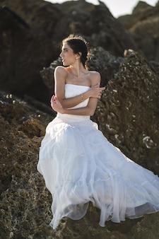 Imagem vertical de uma mulher morena com um vestido branco posando sobre as rochas