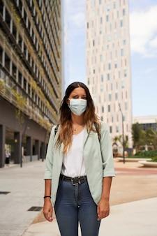 Imagem vertical de uma mulher que trabalha em um centro financeiro usando uma máscara para a pandemia de coronavírus.