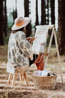 Imagem vertical de uma mulher tecendo uma esteira em um tear caseiro com uma cesta de lã