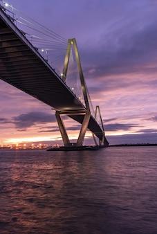 Imagem vertical de uma ponte sobre o mar sob um céu nublado durante o pôr do sol