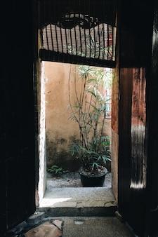 Imagem vertical de uma porta de um prédio antigo sob a luz do sol durante o dia
