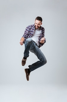 Imagem vertical do homem barbudo na camisa que pulando