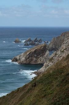 Imagem vertical do mar cercado por rochas cobertas de musgos sob um céu nublado