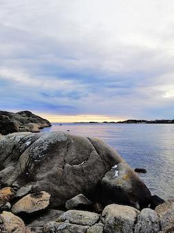 Imagem vertical do mar rodeado por rochas sob um céu nublado durante o pôr do sol na noruega