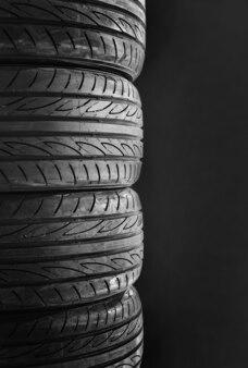 Imagem vertical dos pneus de carro isolados no fundo preto.