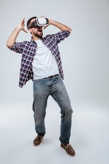 Imagem vertical homem barbudo de camisa usando dispositivo de realidade virtual
