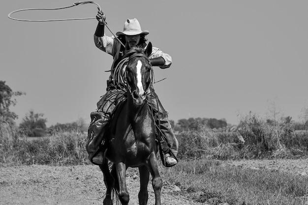 Imagem vintage de um cowboy cavalgando um cavalo e segurando uma corda na mão