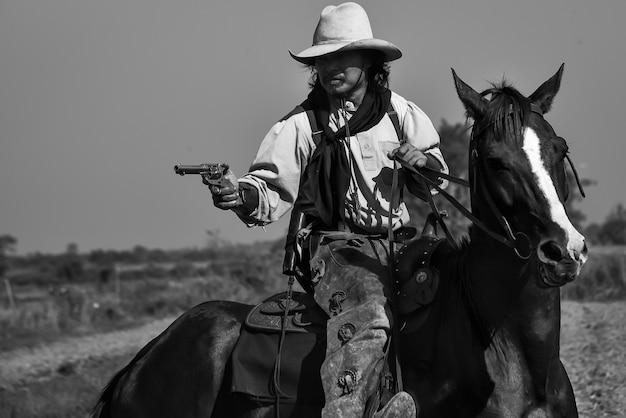 Imagem vintage de um cowboy cavalgando um cavalo e uma arma na mão