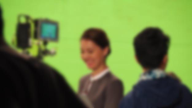 Imagens borradas de fazer um vídeo de filme comercial de tv em um fundo de tela verde grande. equipe da equipe de filmagem trabalhando com o ator. gravação por câmera digital profissional e conjunto de iluminação. filme nos bastidores