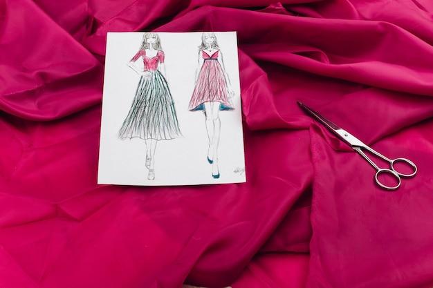 Imagens com modelos de vestido, pano rosa e outros acessórios para artesanato estão na mesa