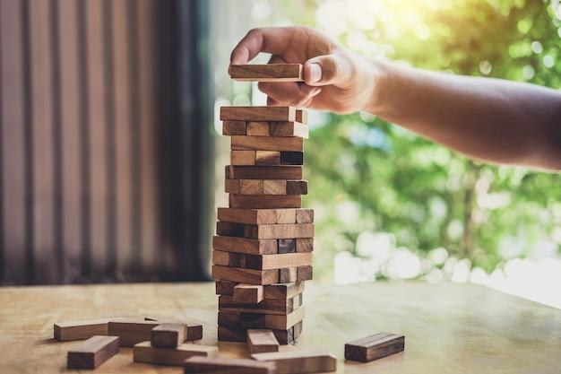 Imagens da mão de empresários colocando e puxando o bloco de madeira na torre