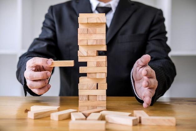 Imagens da mão de pessoas de negócios, colocando e puxando o bloco de madeira na torre