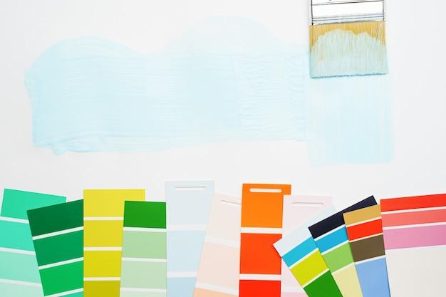 Imagens da paleta com cores azuis e verdes, vermelhas, pincel, sobre fundo branco em branco. lugar para texto.