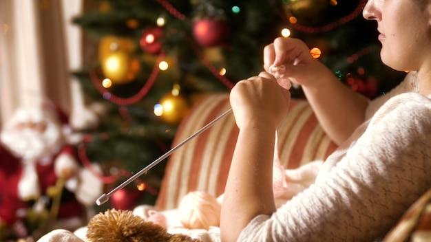 Imagens de 4 k de uma bela jovem sentada na poltrona ao lado da árvore de natal decorada e meias de lã de malha. pessoas relaxando nas férias de inverno e comemorações em casa
