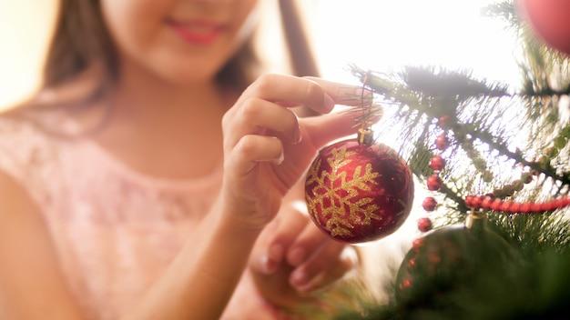 Imagens de 4k de close up de jovem colocando bugiganga vermelha no galho de árvore de natal. família preparando e decorando a casa nas comemorações e feriados de inverno.