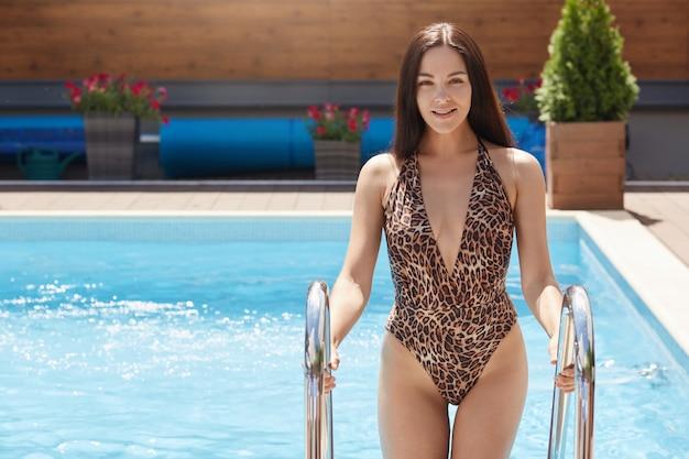 Imagens de alegre morena doce adorável tendo férias, passar os dias de folga com prazer, vestindo roupas de banho de leopardo, segurando escadas, saindo da piscina.