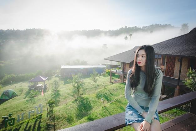 Imagens de belas mulheres asiáticas sentadas em belas atrações naturais mulher asiática com cabelos longos em um tempo frio e nevoento. o fundo é uma acomodação de resort.