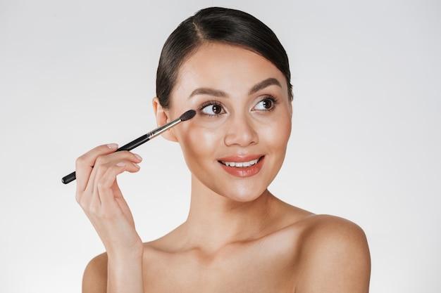 Imagens de beleza da adorável mulher morena, olhando para longe e sorrindo enquanto aplica cosméticos com pincel para sombra, isolado sobre o branco