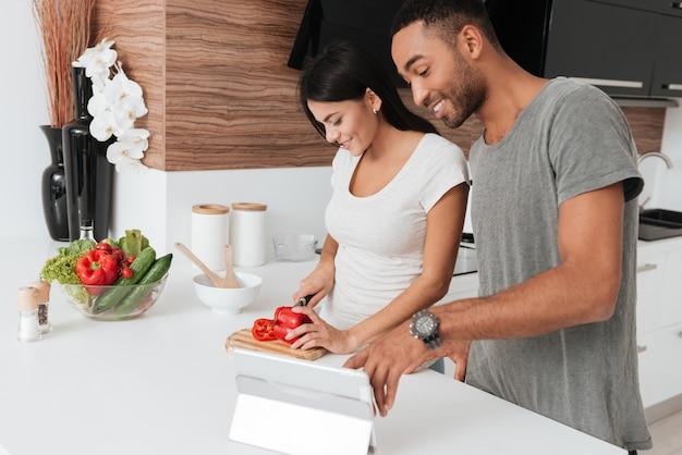 Imagens de casal jovem alegre cozinhando na cozinha usando um computador tablet.