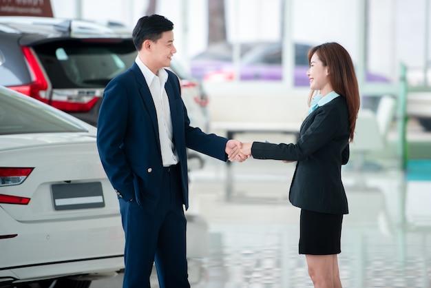 Imagens de clientes e vendedores asiáticos, de mãos dadas, felizes em comprar carros novos que fazem acordos de vendas com revendedores de automóveis.