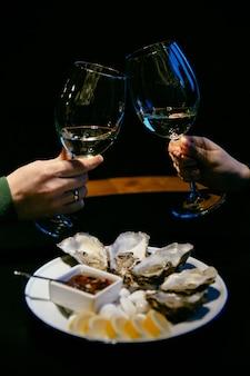 Imagens de close-up da mão feminina e masculina segurar um copos de champanhe