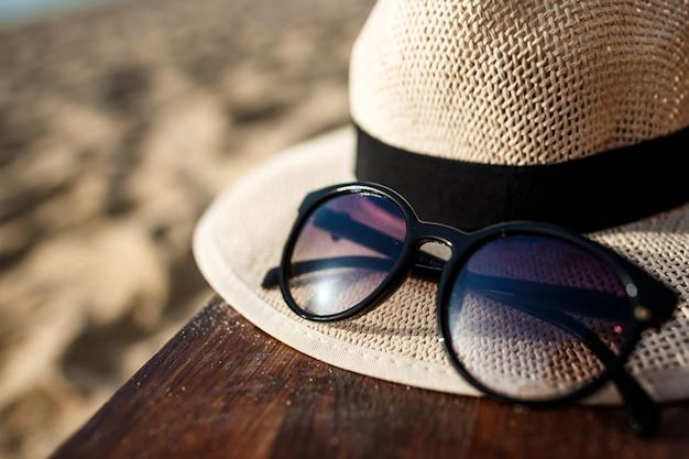 Imagens de close-up de chapéu e óculos na praia