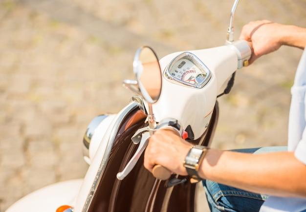 Imagens de close-up de um homem andando de scooter ao ar livre.