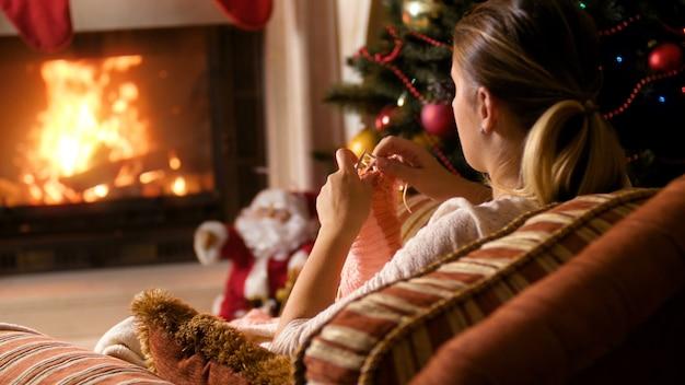 Imagens de closeup 4k de jovem relaxando na poltrona ao lado da lareira a lenha e da árvore de natal brilhante. hobby feminino de tricô